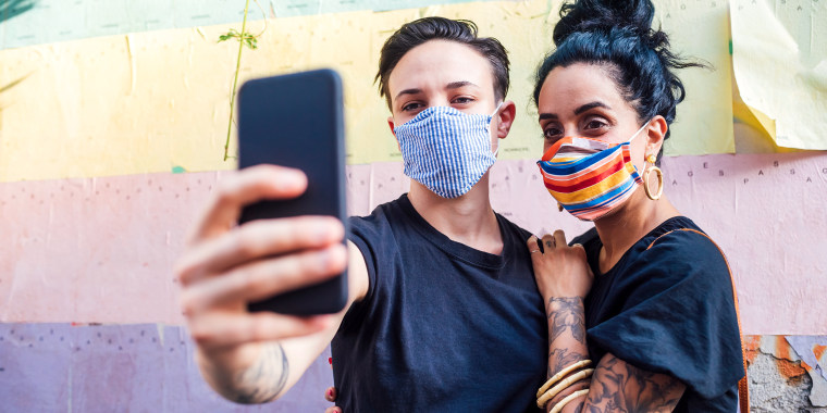 couple wearing colorful face masks taking selfie with smartphone
