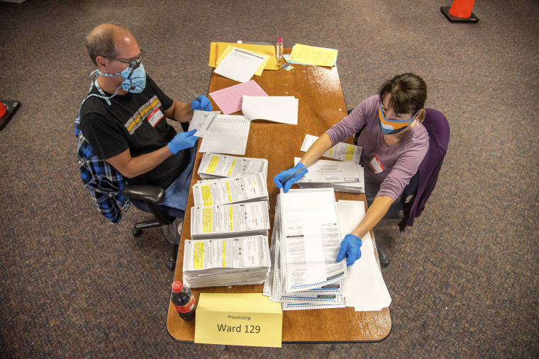 Election workers process absentee ballots at Milwaukee's central count facility on Aug. 11, 2020.