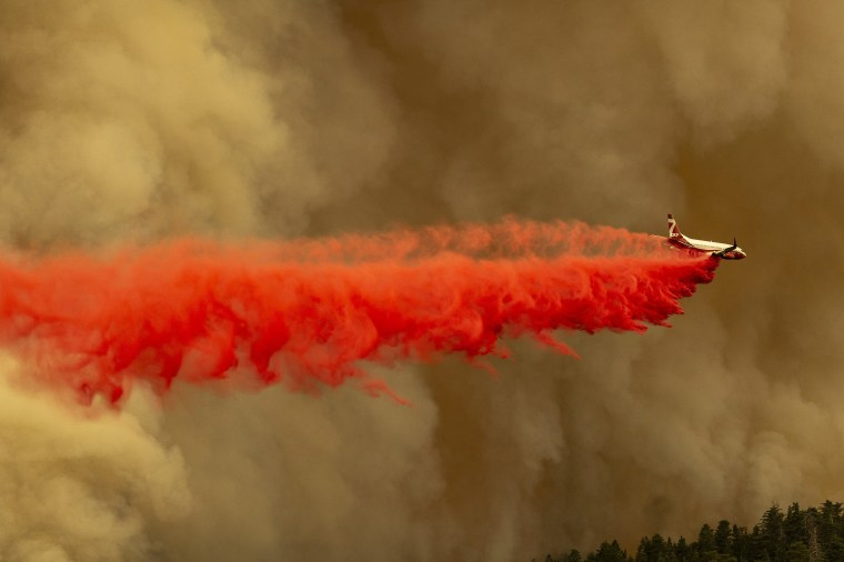 Image: A Coulson 737 firefighting tanker jet drops fire retardant to slow Bobcat Fire at the top of a major run up a mountainside in the Angeles National Forest on Sept.10, 2020 north of Monrovia, CA.