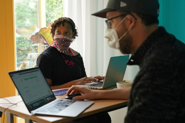 Image: Volunteer Justin Clark (R) guides American citizen Glory Nix through the online voter registration process at a registration drive by the non-partisan group VotefromAbroad.org on Sept. 1, 2020 in Berlin, Germany.