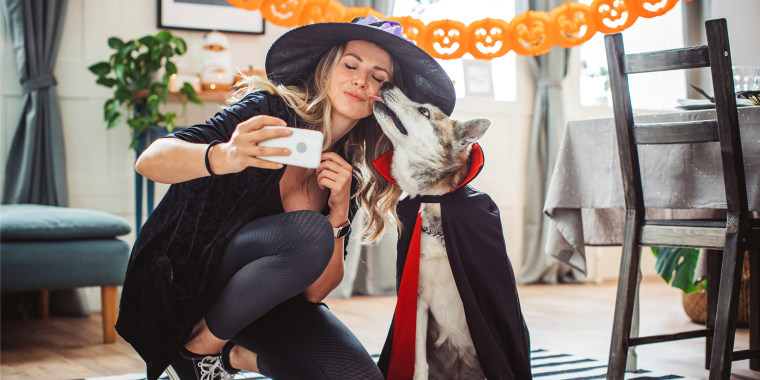 Woman and dog dressed in halloween costumes taking selfie at home