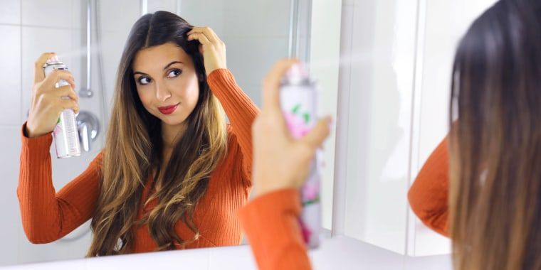 woman spraying dry shampoo in hair in mirror
