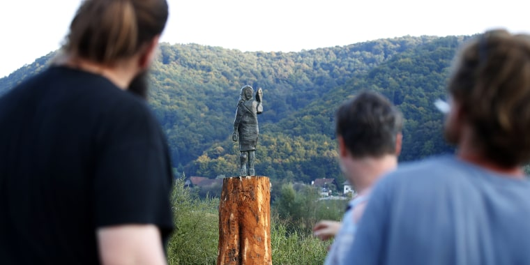 Local people look at a bronze statue representing the U.S first lady Melania Trump in her birthplace of Sevnica, Slovenia on Sept. 15, after a previous one, made in wood, was set alight.