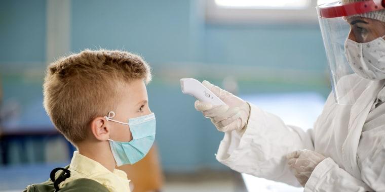 Pediatrician using thermometer temperature screening for school child