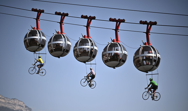 This picture shows cyclists hanging under the Grenoble Bastille cable cars during the 17th stage of the 107th edition of the Tour de France cycling race, 170 km between Grenoble and Meribel, on September 16, 2020.