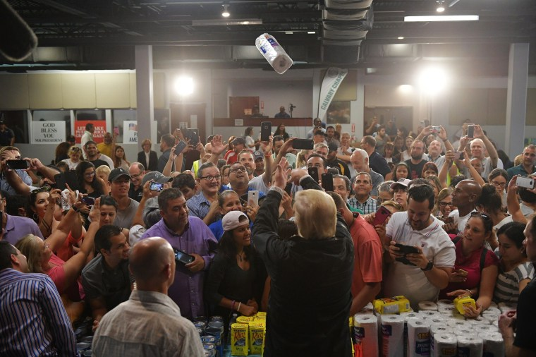 Image: President Donald Trump tosses a roll of paper towels into a crowd