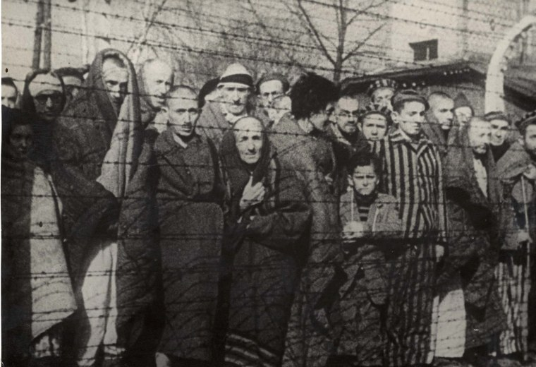 Image: Holocaust survivors stand behind a barbed wire fence after the liberation of Nazi German death camp Auschwitz-Birkenau in 1945 in Nazi-occupied Poland.