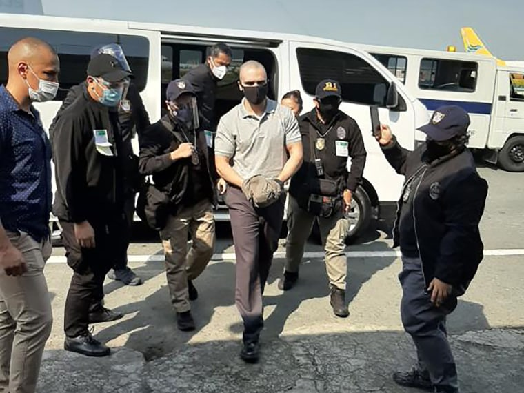 Image: U.S. marine Lance Corporal Joseph Scott Pemberton (C), who was convicted of killing a transgender woman and recently pardoned by Philippine President Rodrigo Duterte, escorted by immigration officers and US personnel as he arrives at the airport in