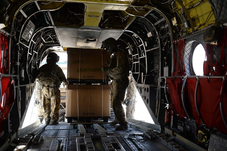Image: U.S. soldiers, part of the NATO-led International Security Assistance Force (ISAF), loading huge boxes into a Chinook helicopter at Bagram Air Field