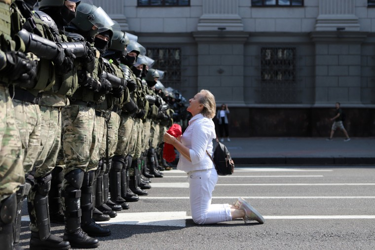 Image: A woman kneels in front of a riot police line as they block Belarusian opposition supporters rally in the center of Minsk, Belarus