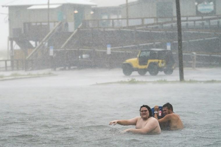 Imagen: La gente juega en un estacionamiento inundado en Navarre Beach, el martes 15 de septiembre de 2020, en Pensacola Beach, Florida.