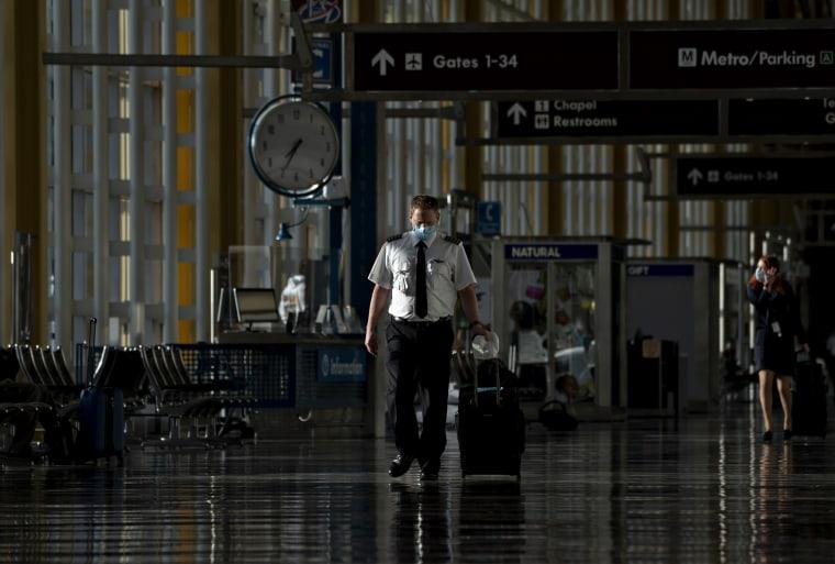 A pilot wearing a protective mask walks through Ronald Reagan National Airport in Arlington