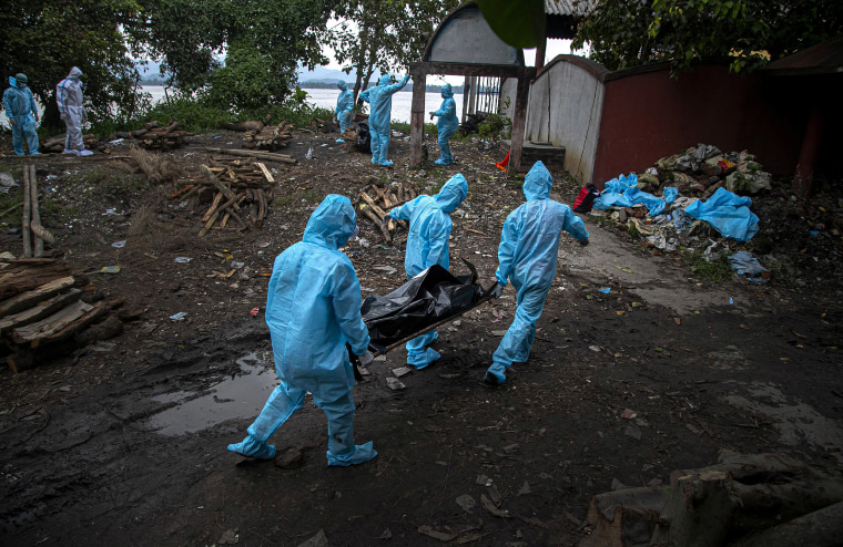 Image: Health workers wearing personal protective equipment carry the body of a COVID-19 victim for cremation in Gauhati, India,