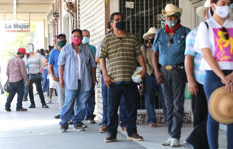 Image: People wear face coverings while waiting in a socially distanced line to enter a bookkeeping shop near the U.S.-Mexico border in Imperial County, which has been hard-hit by the COVID-19 pandemic