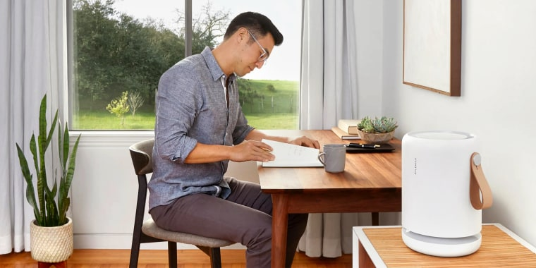 man working from home with air purifier on desk. With COVID-19 cases in the U.S. growing each day and  West Coast fires, breathing safely is a top concern. Shop fast-shipping air purifiers from brands like Dyson, Honeywell and more.