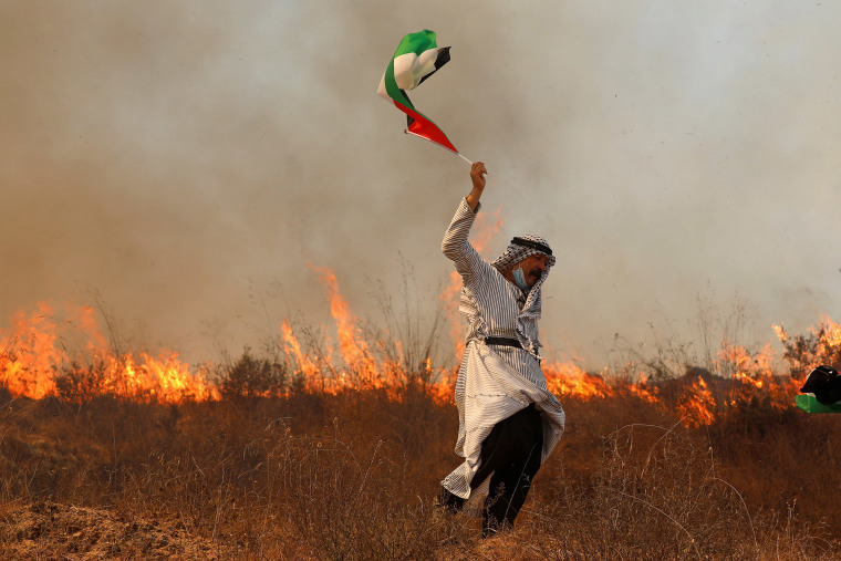 Image: A demonstrator holds a Palestinian flag in front of a fire during protest against Jewish settlements and normalizing ties with Israel, in Asira al-Qibliya in the Israeli-occupied West Bank
