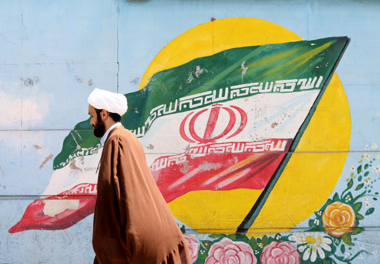 Image: An Iranian cleric walks past a mural painting of the national flag in the capital Tehran.