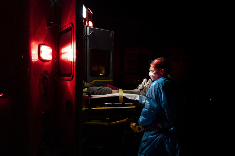 A paramedic places a patient with Covid-19 symptoms inside an ambulance in Brooklyn Park, Md.
