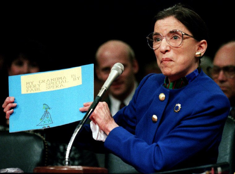 """Image: US Supreme Court nominee Ruth Bader Ginsburgh holds up a drawing of herself with the words \""""My Grand.."""