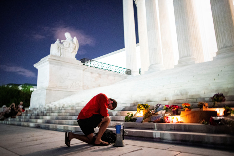 Image: A man kneels as he brings a megaphone to a vigil on the steps of the U.S. Supreme Court following the death of U.S. Supreme Court Justice Ruth Bader Ginsburg, in Washington