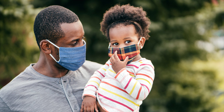 father holding young daughter outside wearing face masks