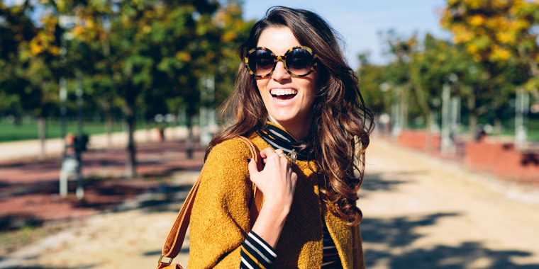 woman smiling outside wearing yellow fall jacket
