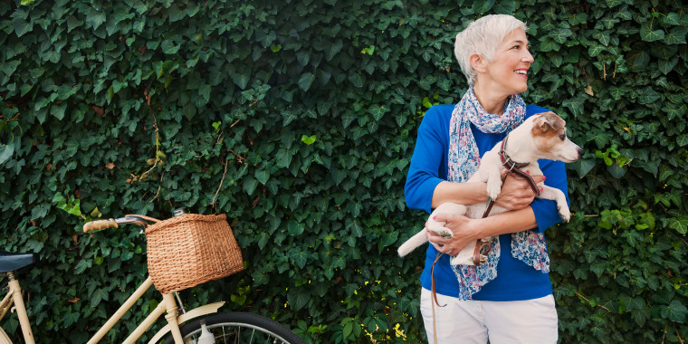 woman wearing summer fall transitional clothing outside with dog and bike
