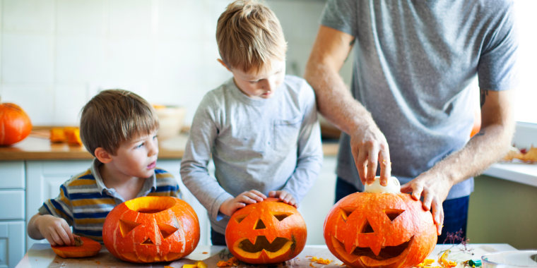 father and sons carving halloween pumpkins in kitchen