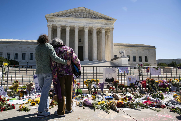 Image: Women embrace at a makeshift memorial for late Supreme Court Justice Ruth Bader Ginsburg on the steps of the United States Supreme Court