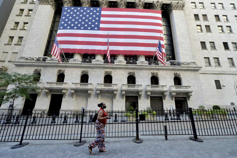 A woman wearing a face masks walks past a large American flag on the facade of the New York Stock Exchange in New York, NY, September 8, 2020. Stocks closed lower as the DOW dropped 630 points due in part to fears of a COVID-19 resurgence and the economic effect it could have on the economy. (Anthony Behar/Sipa USA)(Sipa via AP Images)