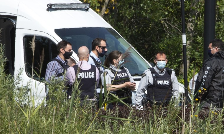 Image: Royal Canadian Mounted Police officers gather outside an apartment complex during a raid in connection with the mailing of ricin to President Trump, Monday, September 21, 2020 in St-Hubert, Quebec.