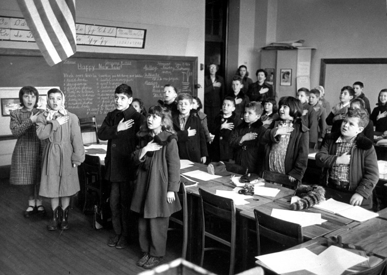 School children wearing coats against th