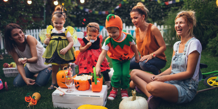adults and children throwing backyard halloween party at home