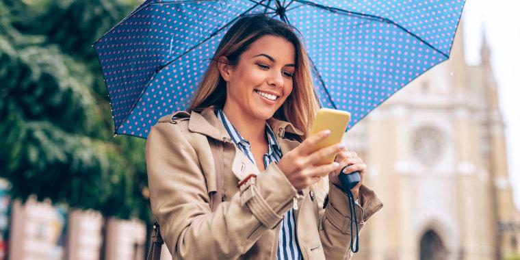 woman wearing rain jacket in rain holding umbrella and smartphone