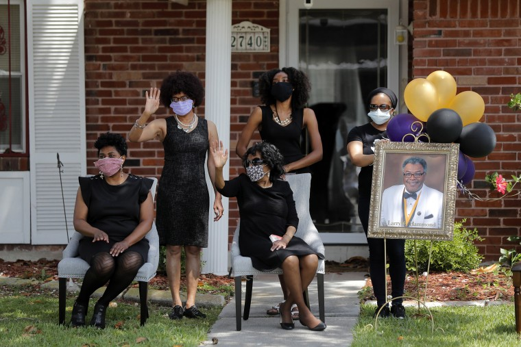 Image: The family of Larry Hammond wave as a line of cars with friends and family, who could not attend his funeral due to the coronavirus, pass by their home, in New Orlea