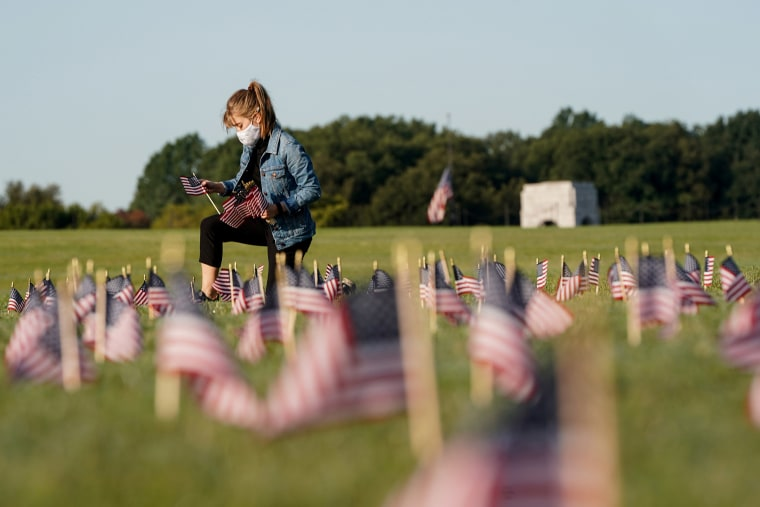 Image: A volunteer places American flags representing some of the 200,000 lives lost in the United States in the coronavirus disease (COVID-19) pandemic on the National Mall in Washington