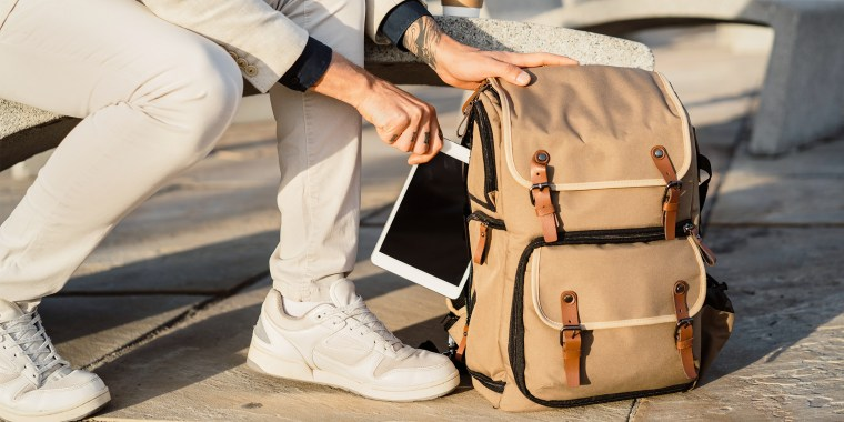 man pulling tablet out of backpack
