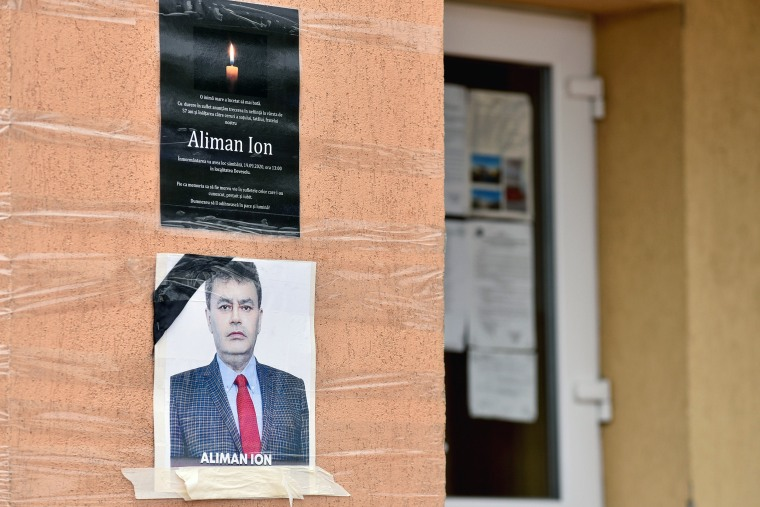 Image: An obituary photo of former mayor Aliman Ion is taped onto the walls of the city hall in Deveselu
