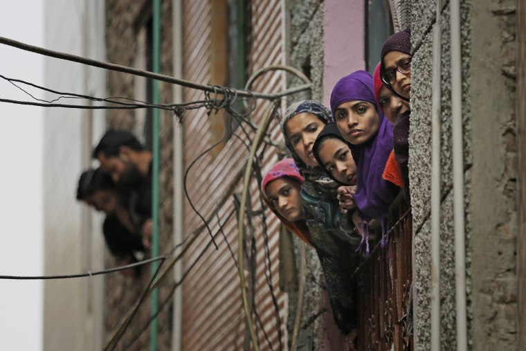 Image: Indian Muslim women look out of a window as security officers patrol a street in New Delhi, India