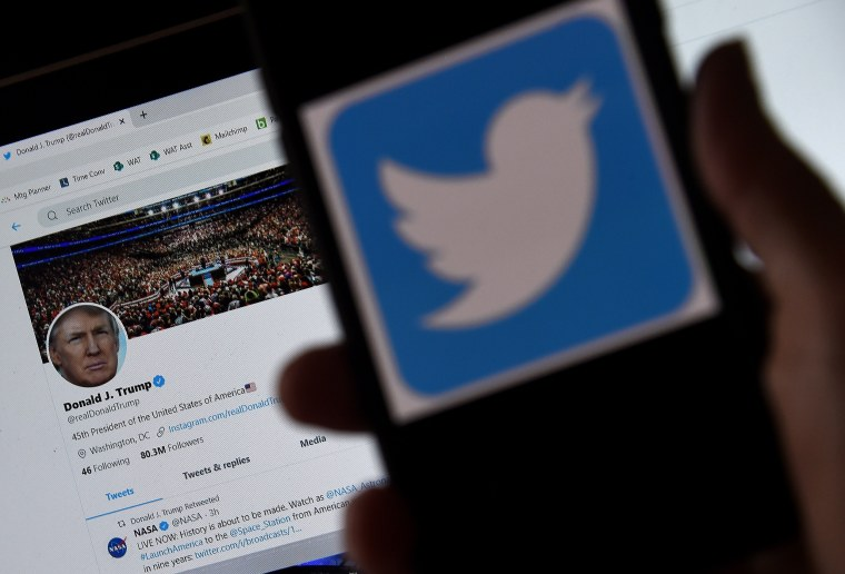 Image: A Twitter logo is displayed on a mobile phone with President Trump's Twitter page shown in the background