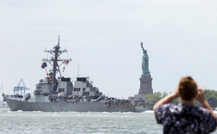 A woman photographs the the USS Stout, of the United States Navy, as it sails past the Statue of Liberty during the parade of ships in New York Harbor for Fleet Week