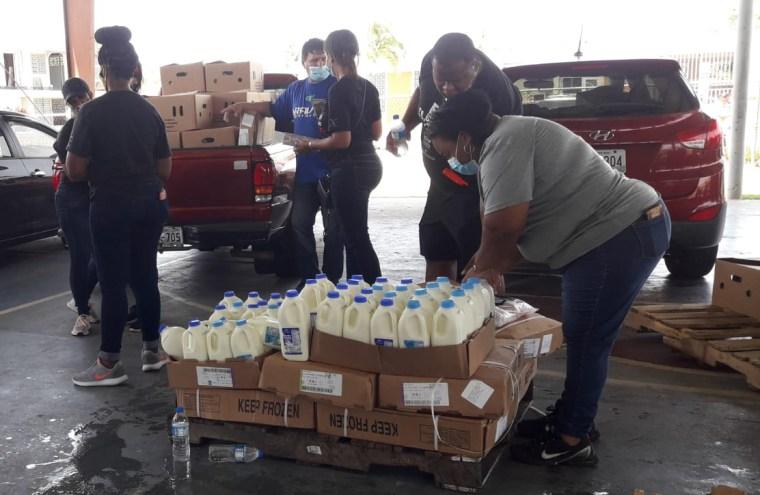 Volunteers help distribute milk in Loiza, Puerto Rico.