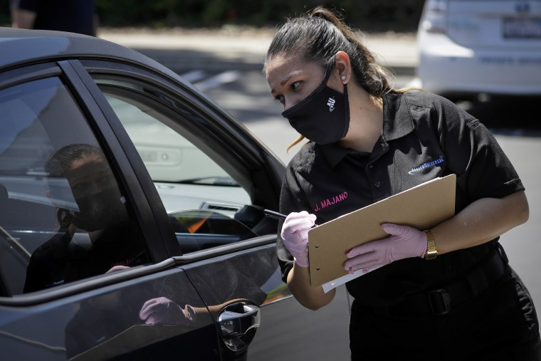 Jennifer Majano helps a job seeker fill out an application at a drive-up job fair for Allied Universal on May 6, 2020, in Gardena, Calif.