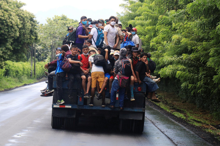 Image: Honduran migrants trying to reach the U.S. hitchhike on a truck after bursting through a border checkpoint to enter Guatemala illegally, in Entre Rios