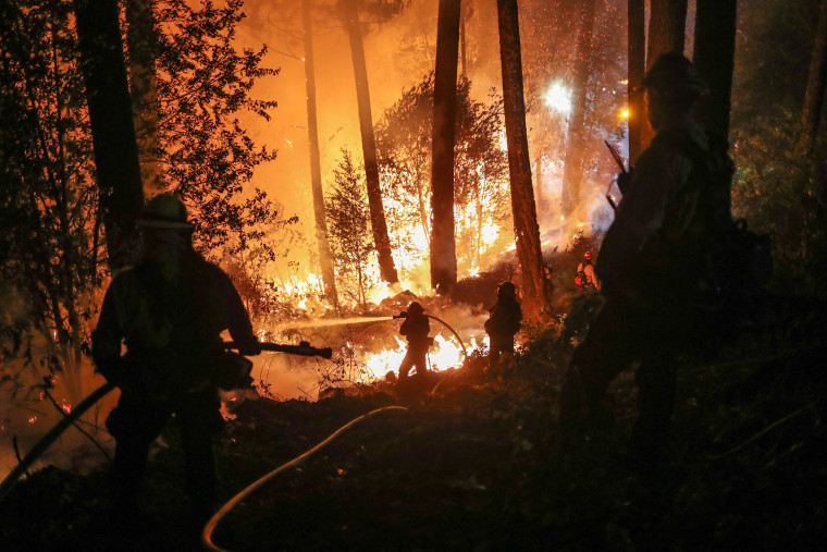 Image: Firefighters battle the Glass Fire as it encroaches towards a residence in Calistoga, California