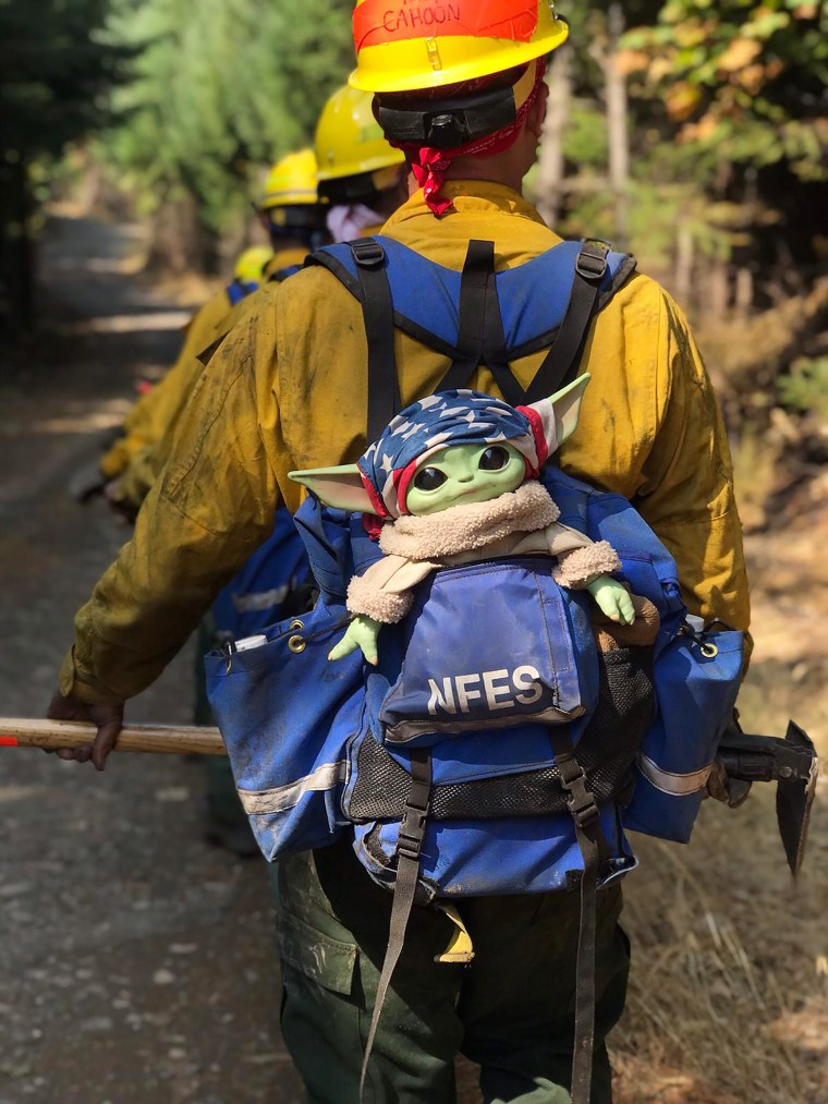 "A Baby Yoda doll, from the sci-fi series ""The Mandalorian,"" hitches a ride in the backpack of an Oregon Air National Guard firefighter on Sunday, Sept. 20, 2020 while fighting the Holiday Farm Fire in Blue River, Oregon.  (Courtesy of Jaebyn Drake via AP)"