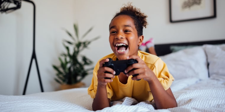 Cheerful young African American girl playing video games