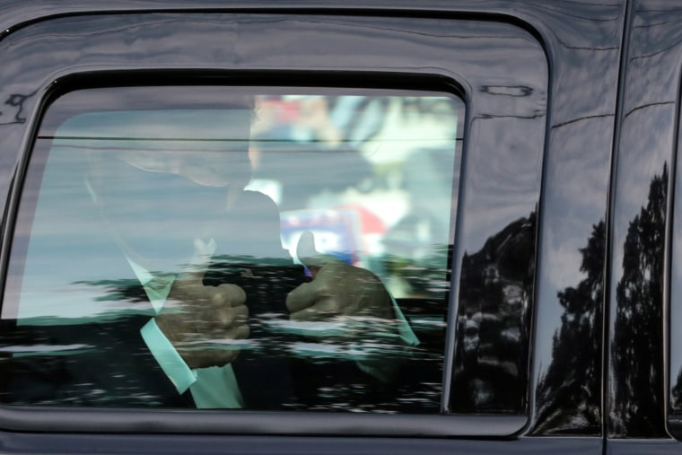 Image: President Donald Trump gives thumbs up to supporters as he rides by in the presidential motorcade in front of Walter Reed National Military Medical Center, where he is being treated for coronavirus disease (COVID-19) in Bethesda, Maryland