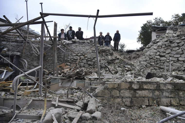 Image: Men look at the damage in a residential area after shelling by Azerbaijan's artillery during a military conflict in self-proclaimed Republic of Nagorno-Karabakh, Stepanakert