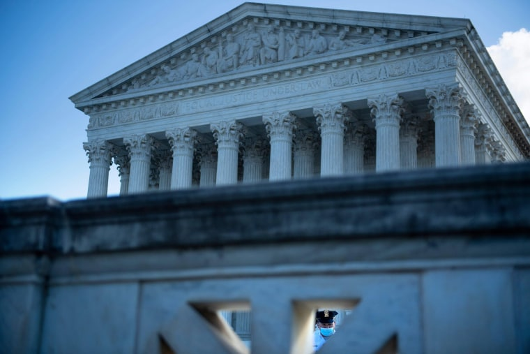 Image: A guard is seen wearing a mask in front of the U.S. Supreme Court Oct. 2, 2020, in Washington.